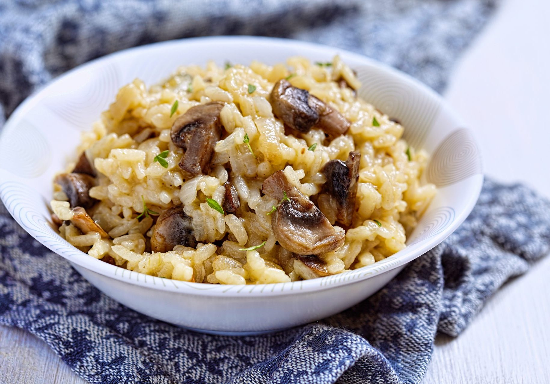 rice with mushrooms in a bowl on a blue napkin