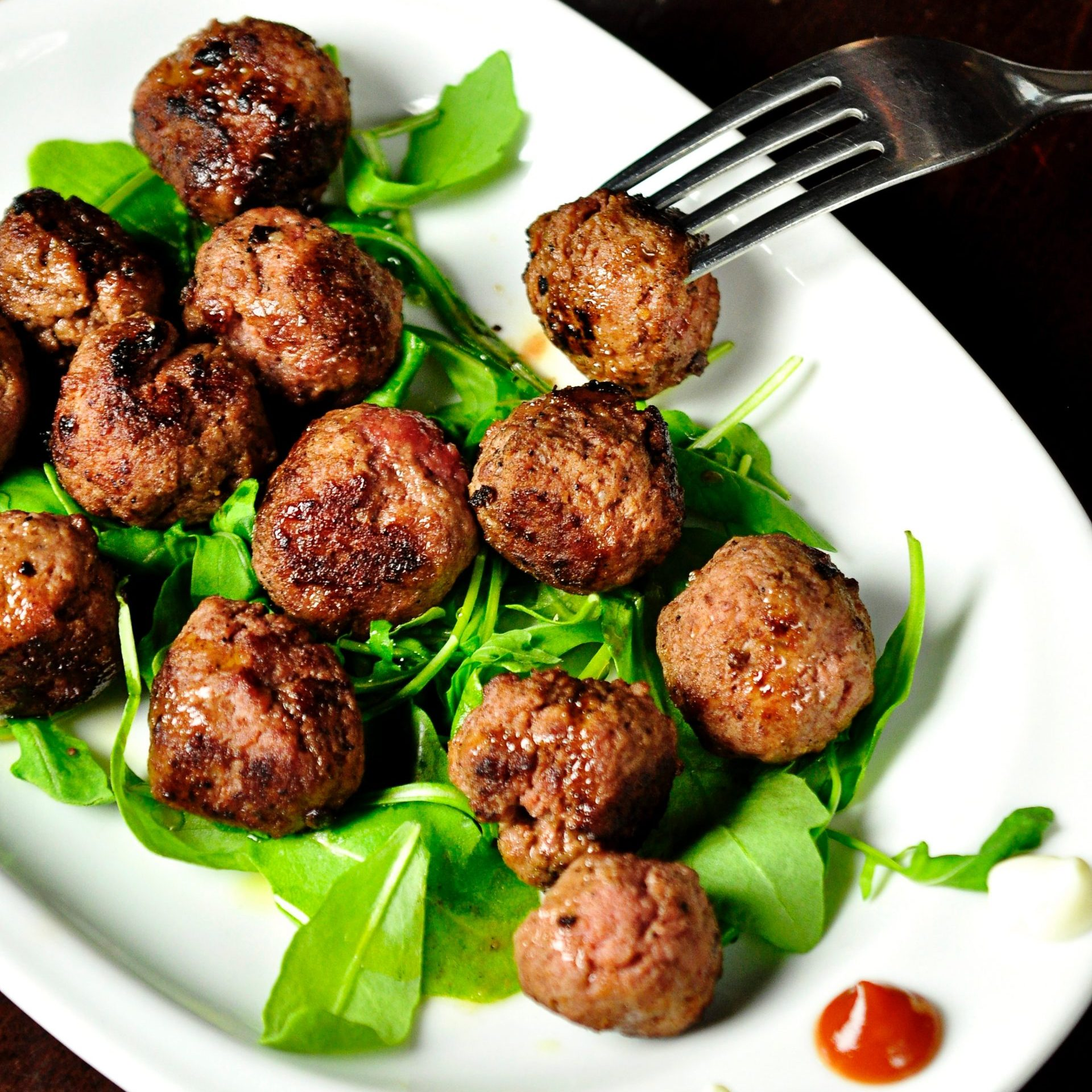 Meatballs with some salad leafs on a white board. Someone pulling a fork in one meatball