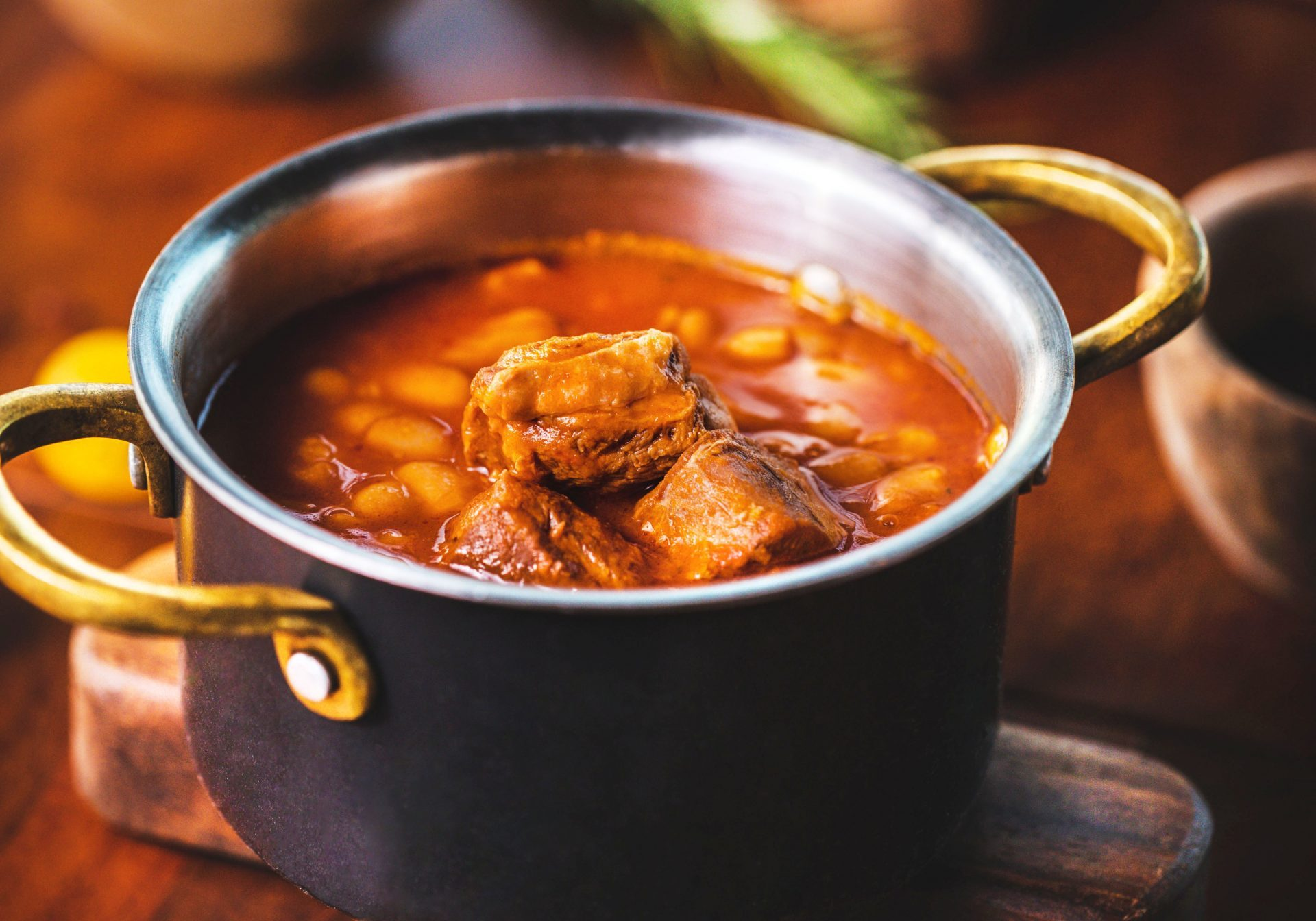 red soup with beans and meat in a pan, standing on a wooden table with rosemary