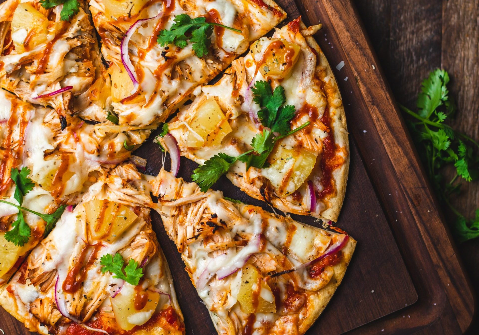 sliced ready meal pizza with some herbs and onions aside on a wooden board on wooden background