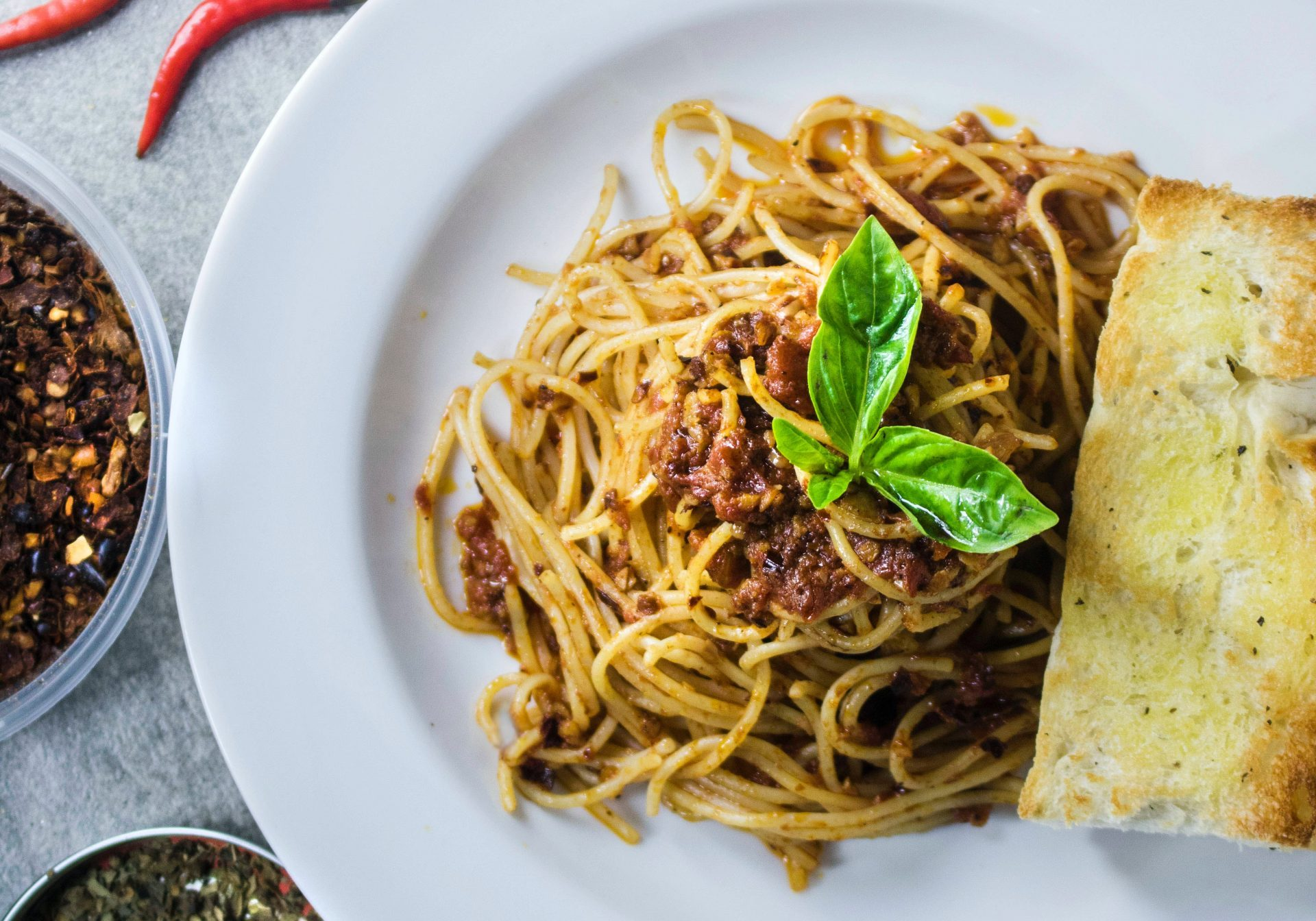 Spaghetti with a brown sauce and some herbs and bread on a white plate