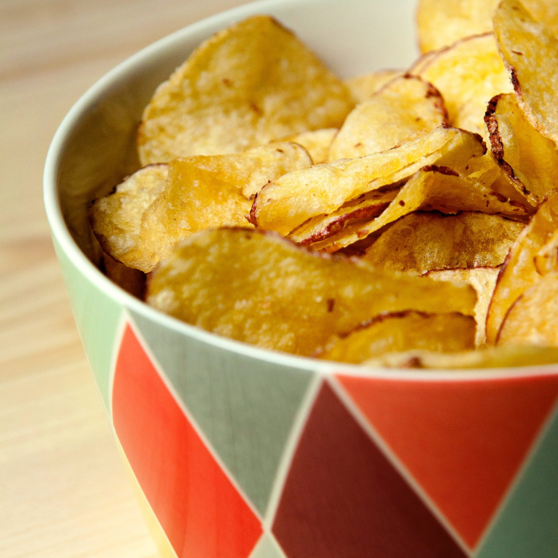 potato crisps chips in a colorful bowl on a wooden table