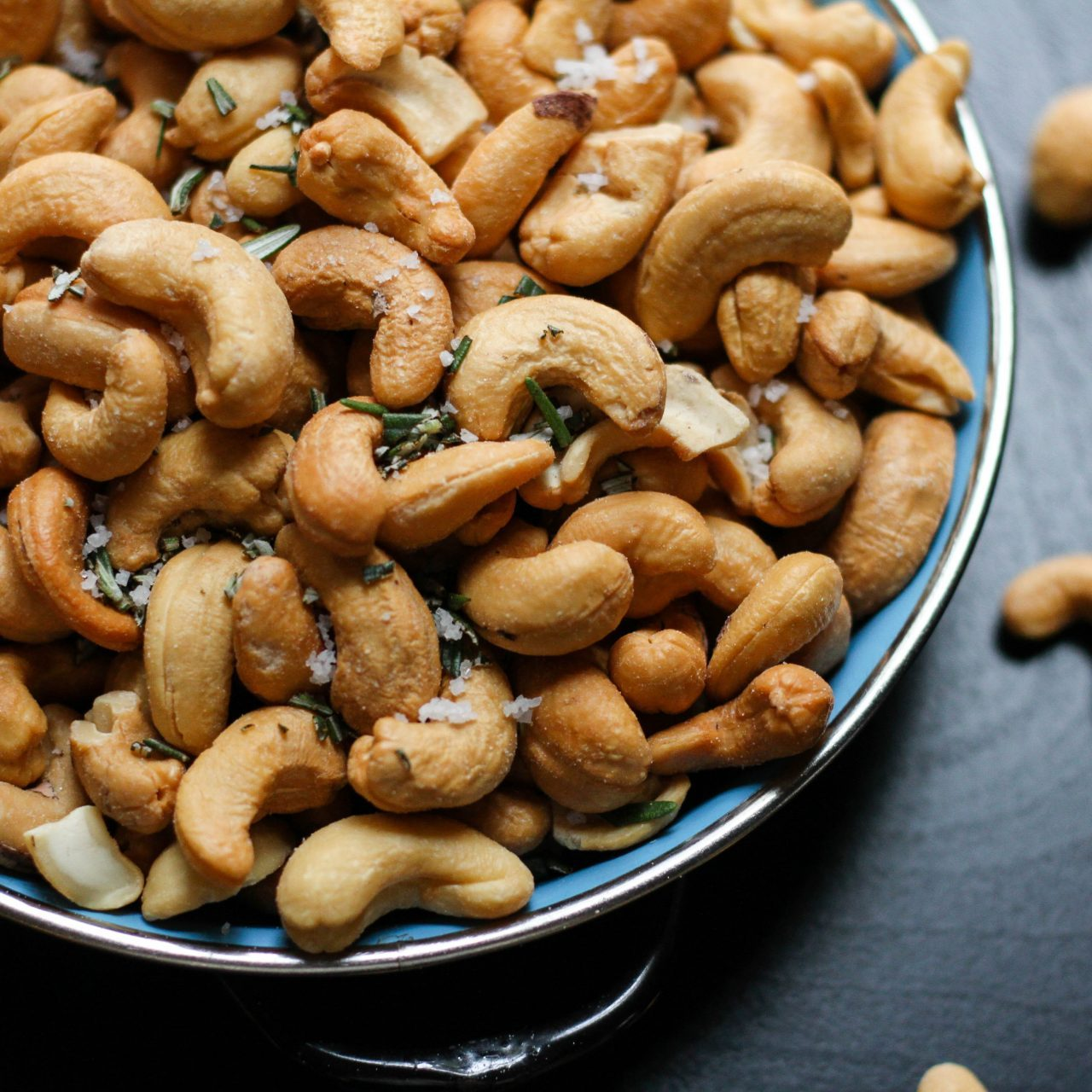 Cashews on a plate on dark background cold snacks