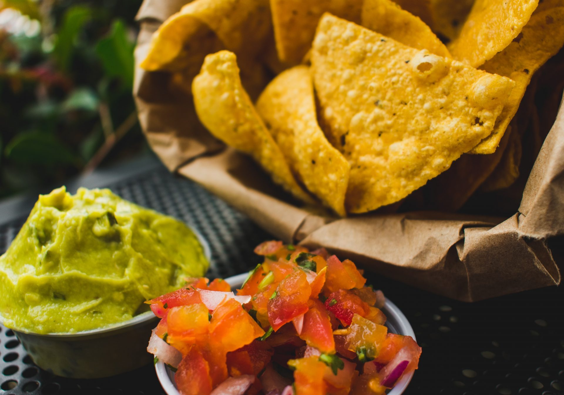 nachos with guacamole and tomatoes on a garden table
