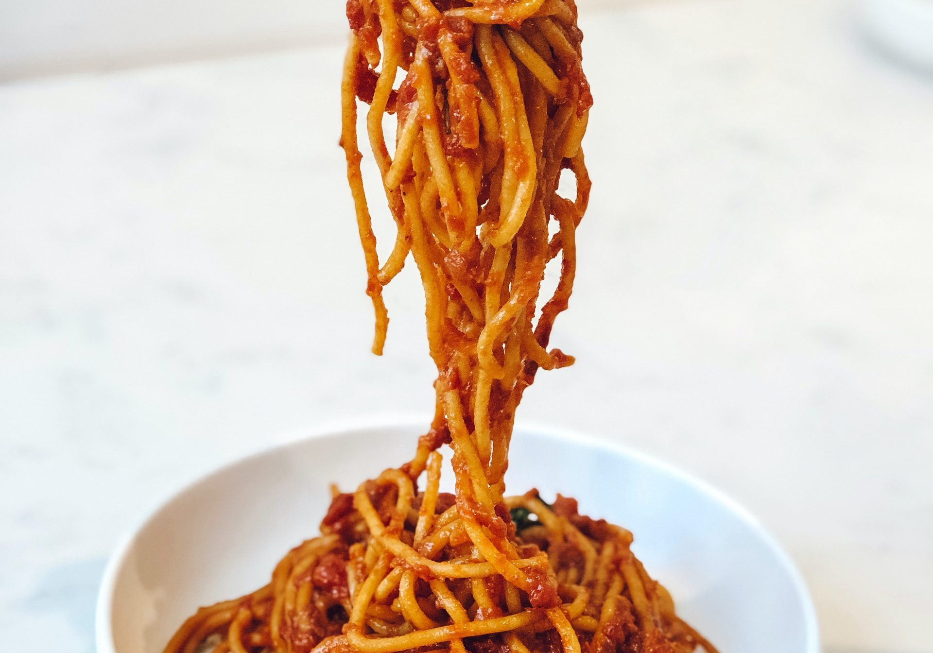 Spaghetti with tomato sauce in a white bowl on white background