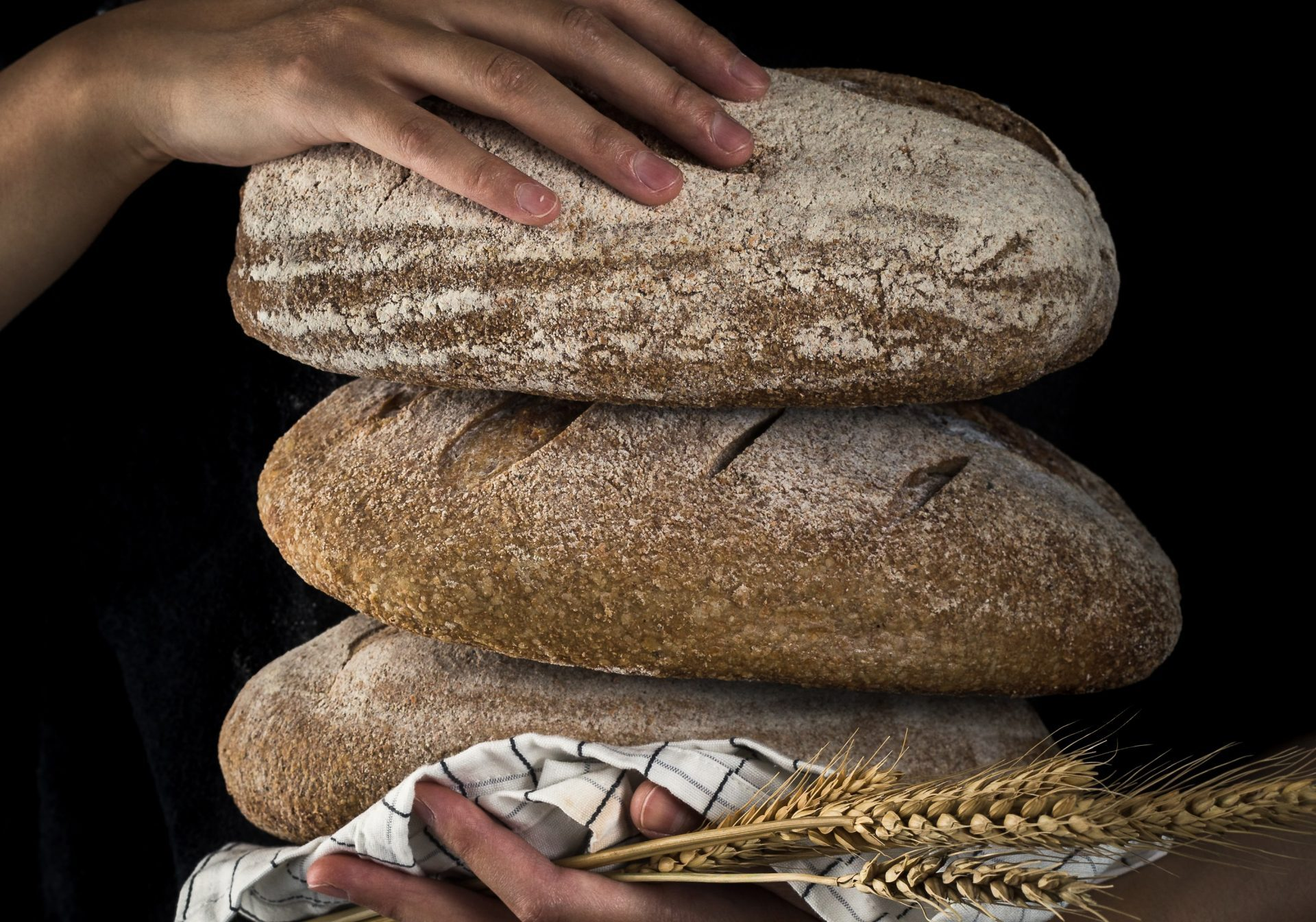 baking three different sorts of bread in. the hands of a woman, black background