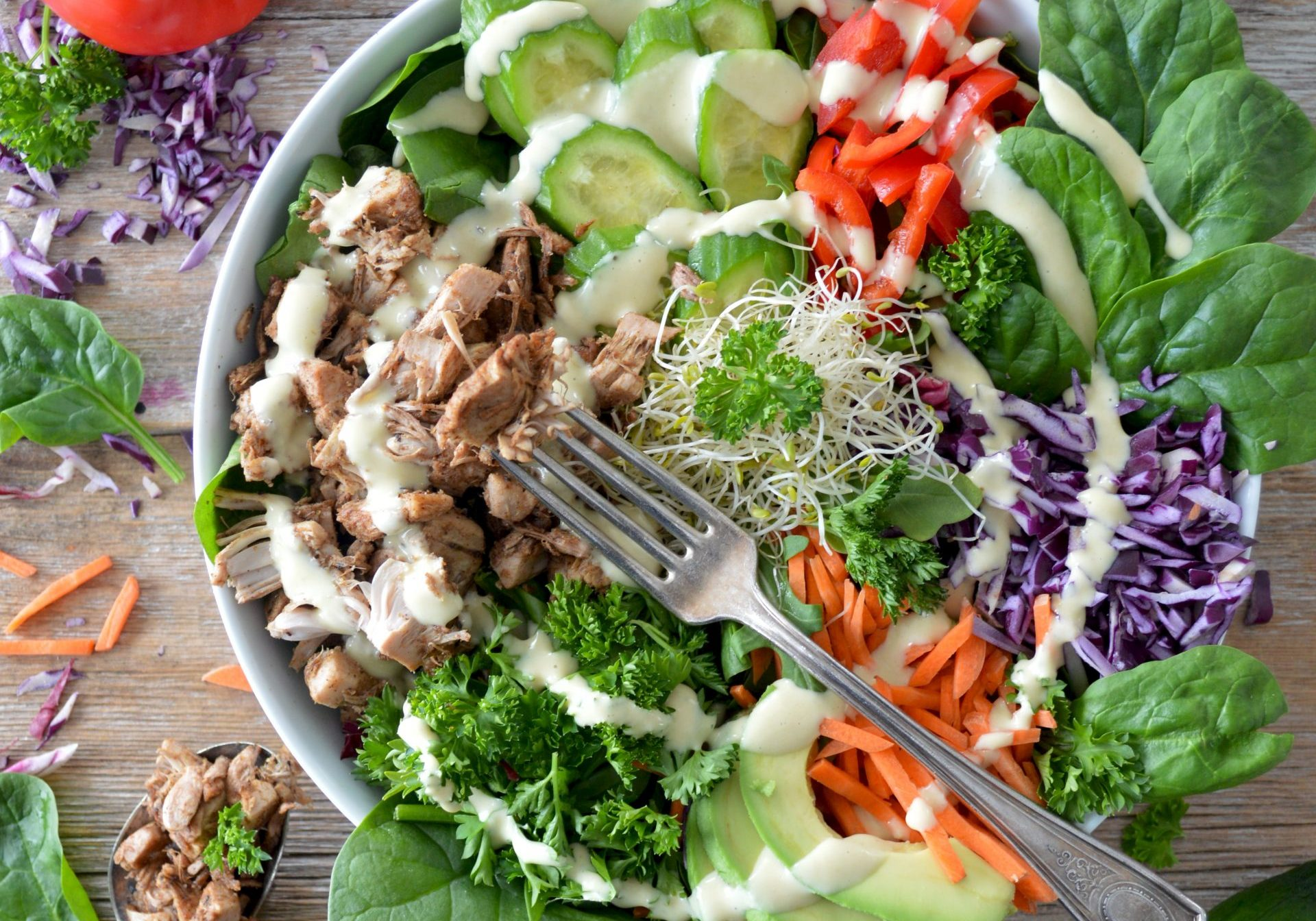 Huge salad bowl with vegetables and meat with dressing on it