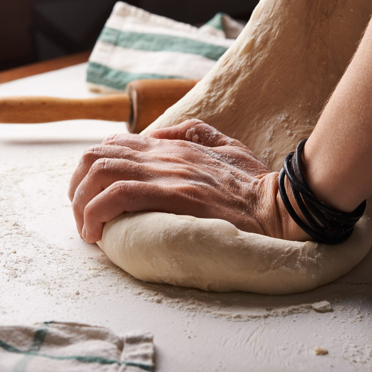 A hand kneading dough on a table