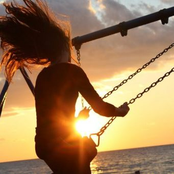Scelta Inside woman sitting on a swing while the sun is going down sunset health healthy vitamin d