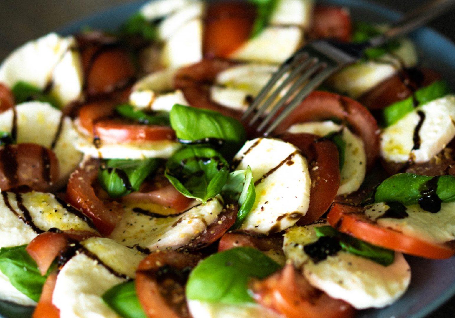 Insalata Caprese with dressing. Tomato, Basil and mozzarella lying on a blue plate