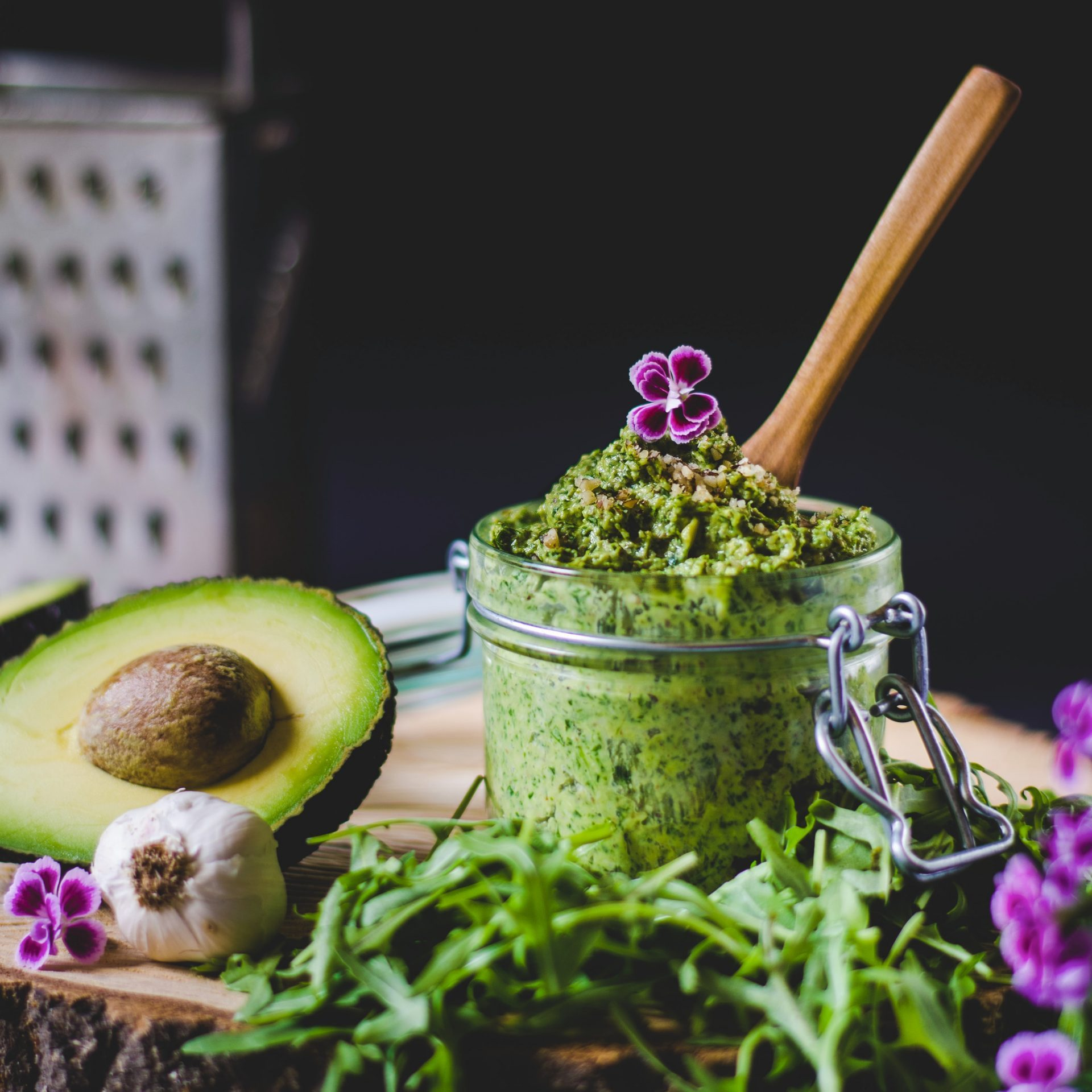 Green pesto in a glass with a wooden spoon in it. Rocket, avocado and some garlic lying next to it.