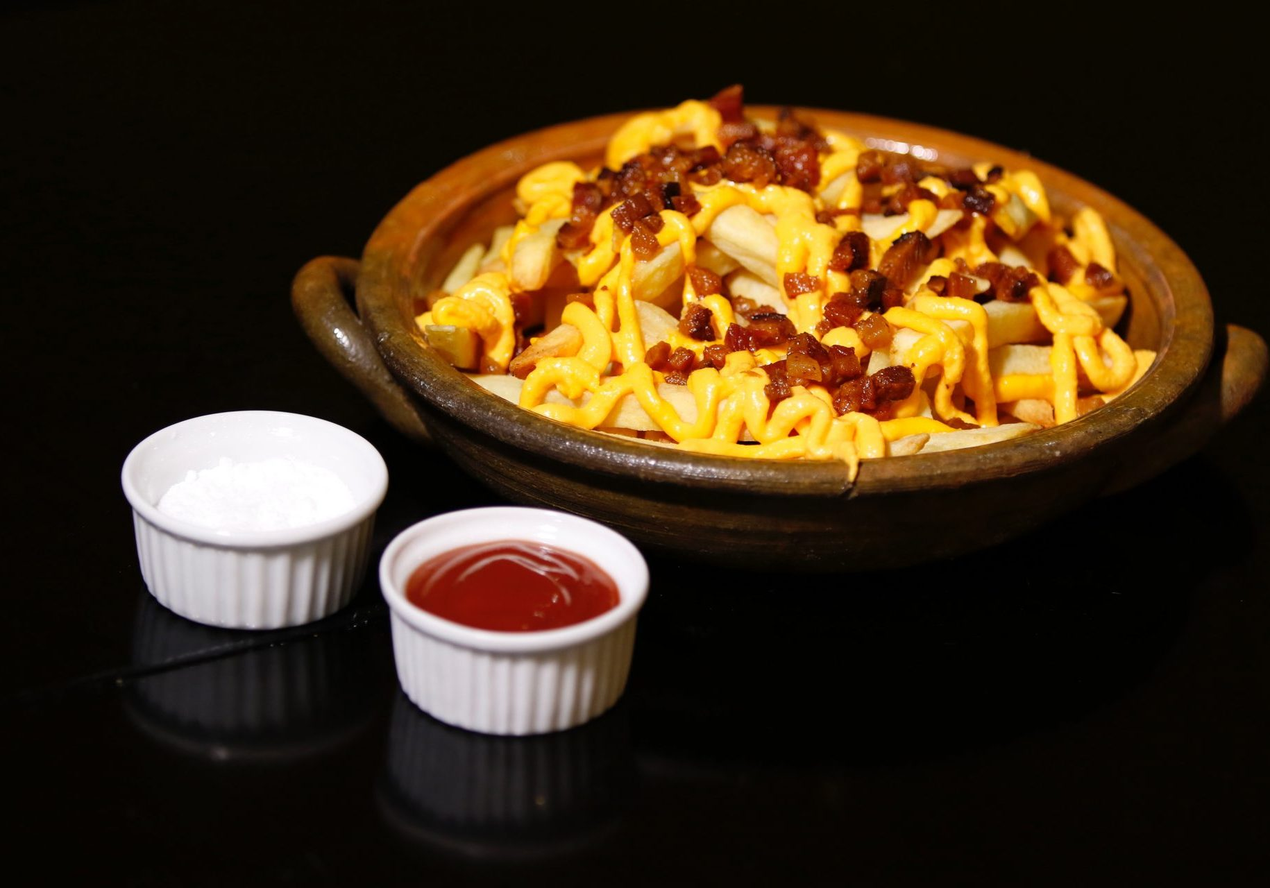 chill cheese fries with bacon and two table sauce with black background