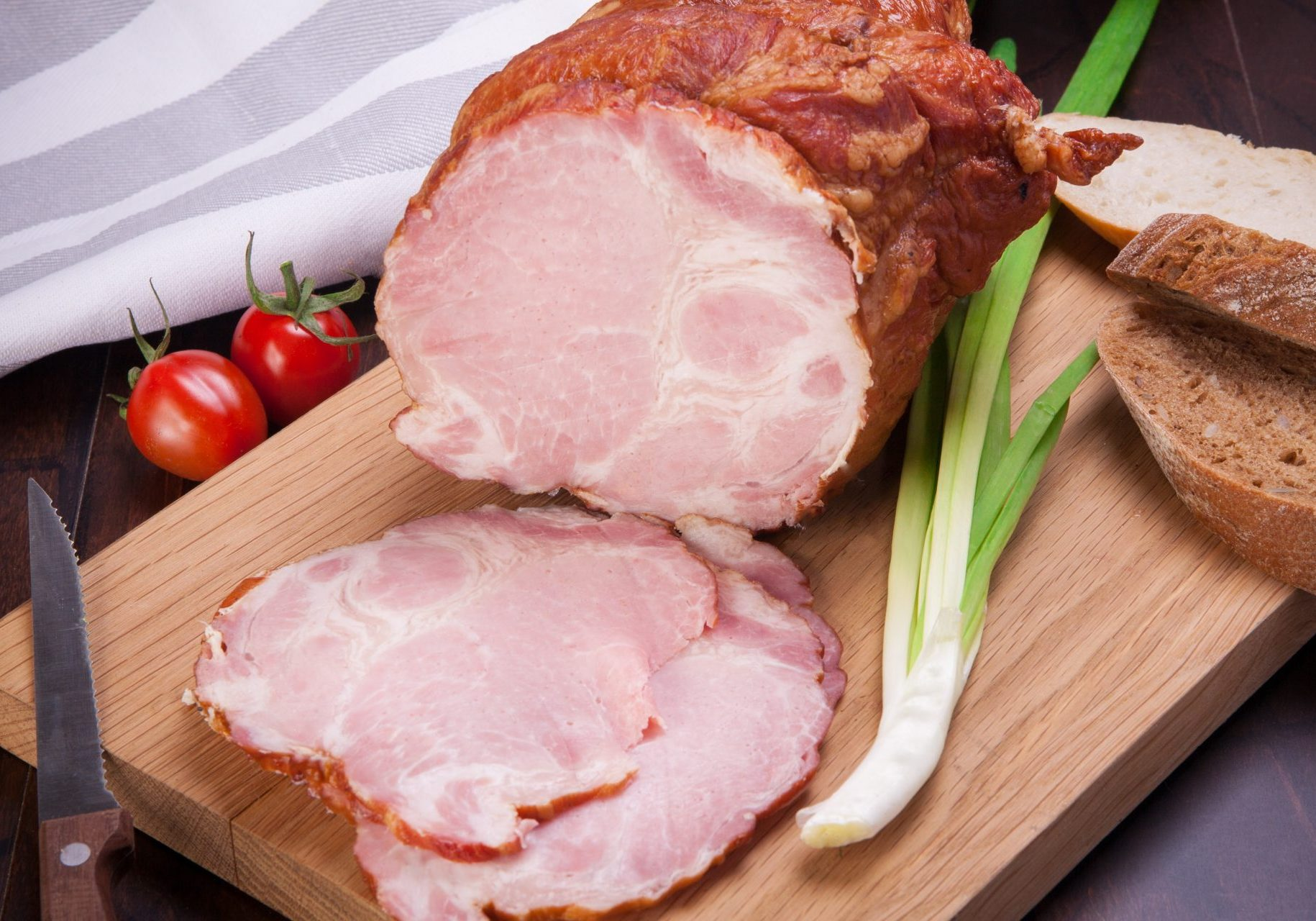 Ham meat with leek and tomatoes lying on a wooden board