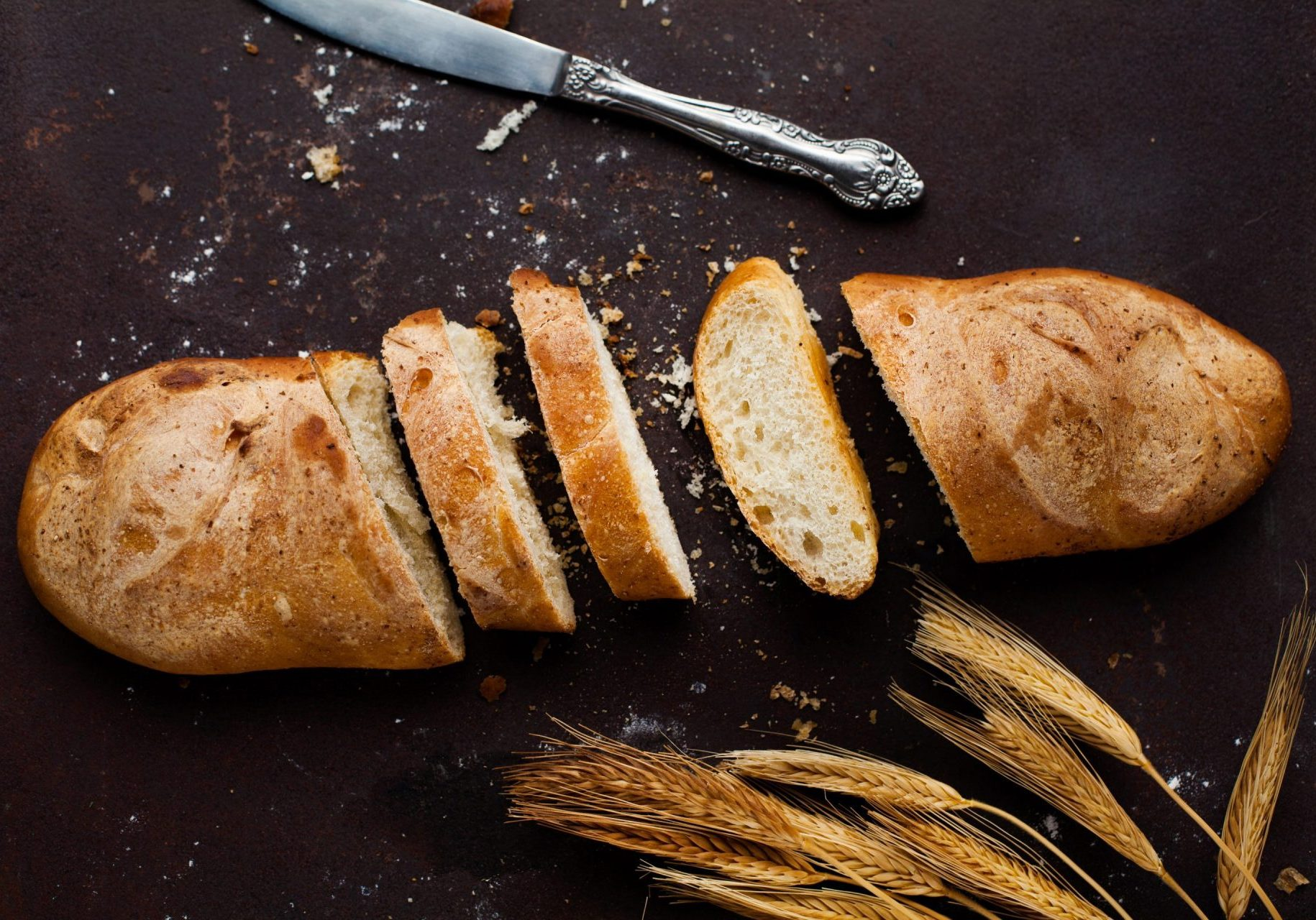 Baking Baguette with three slices and a knife lying on a dark background