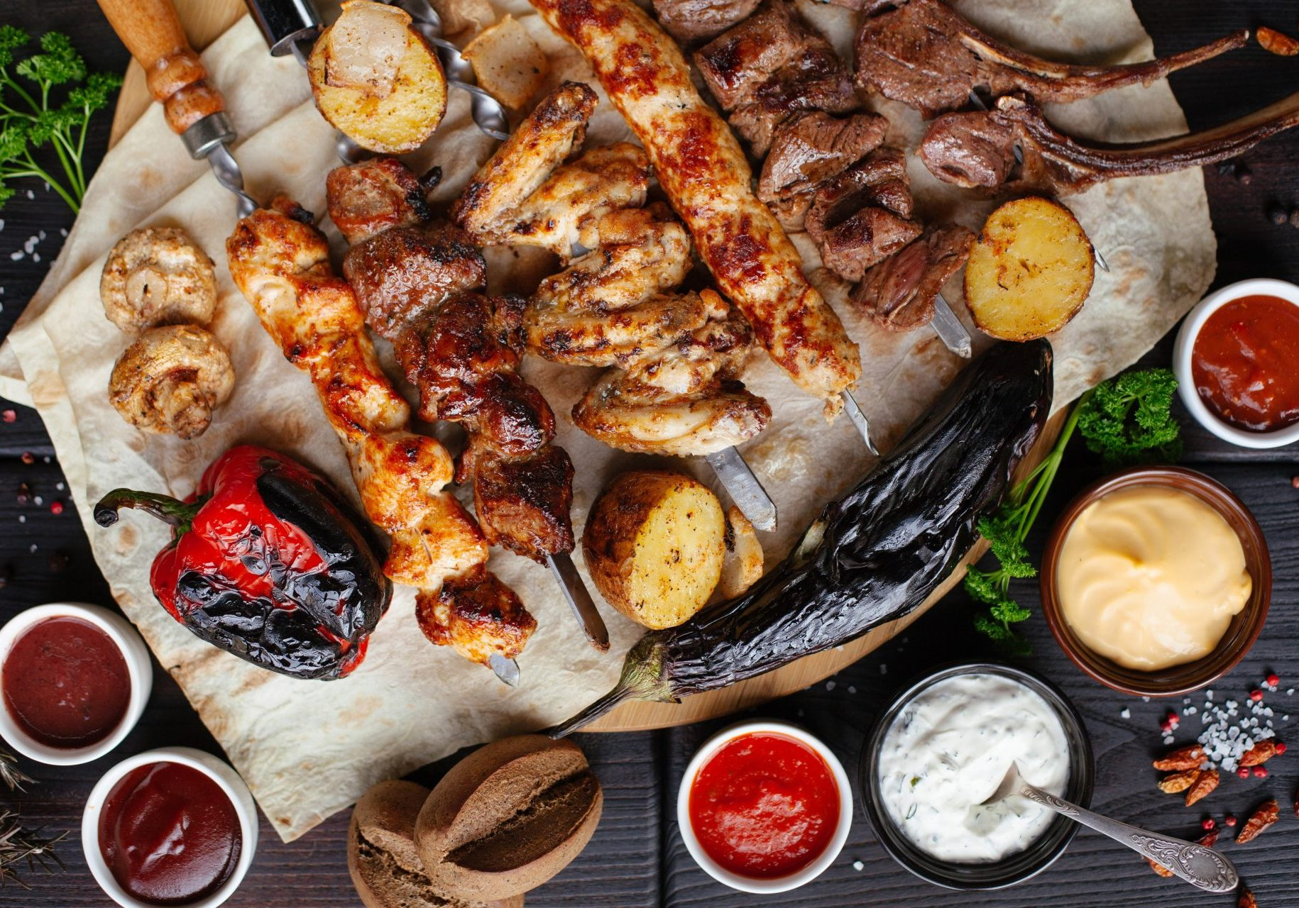 Barbecue meat and sausages with vegetables and dips on a black background